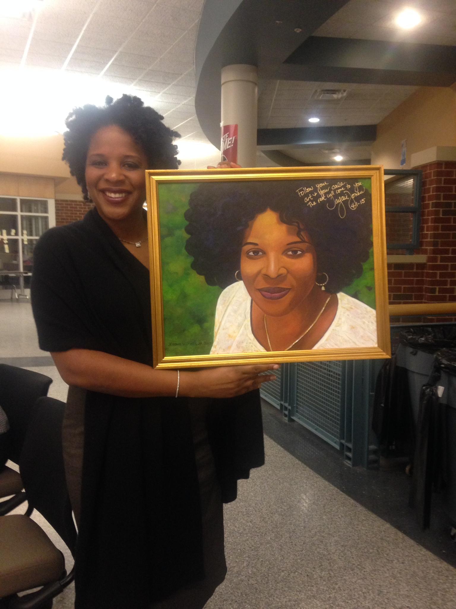IMG: Tayari Jones holding a painting of herself.