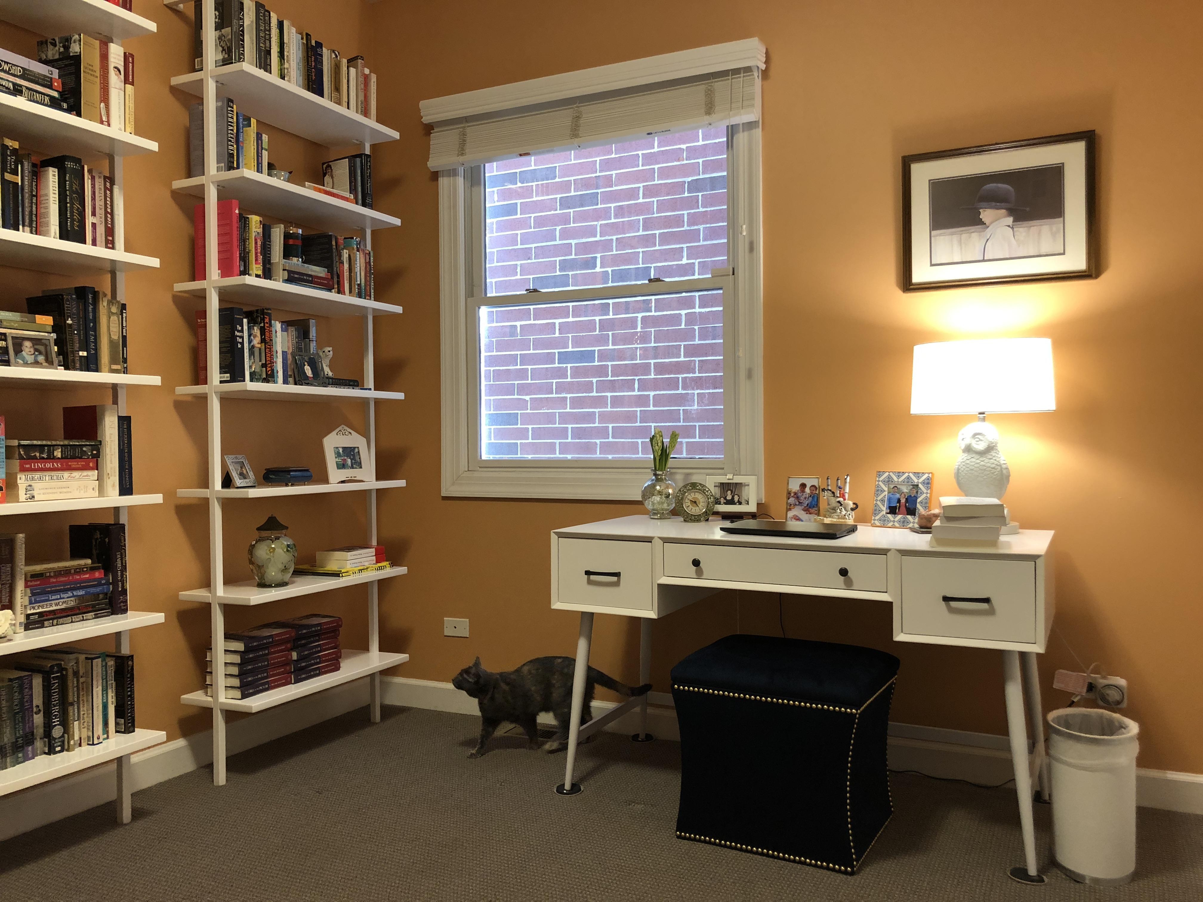 Melanie Benjamin's workspace. A desk faces a wall near an open window.