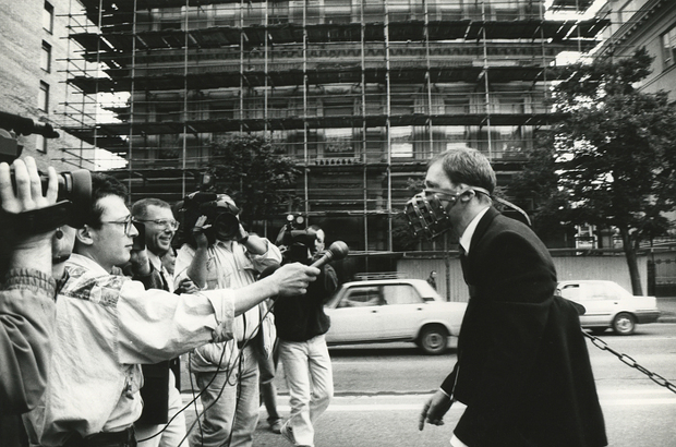 Reporters holding microphones out to a man in a mask.