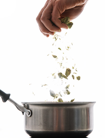 Hops being dropped into a pot.