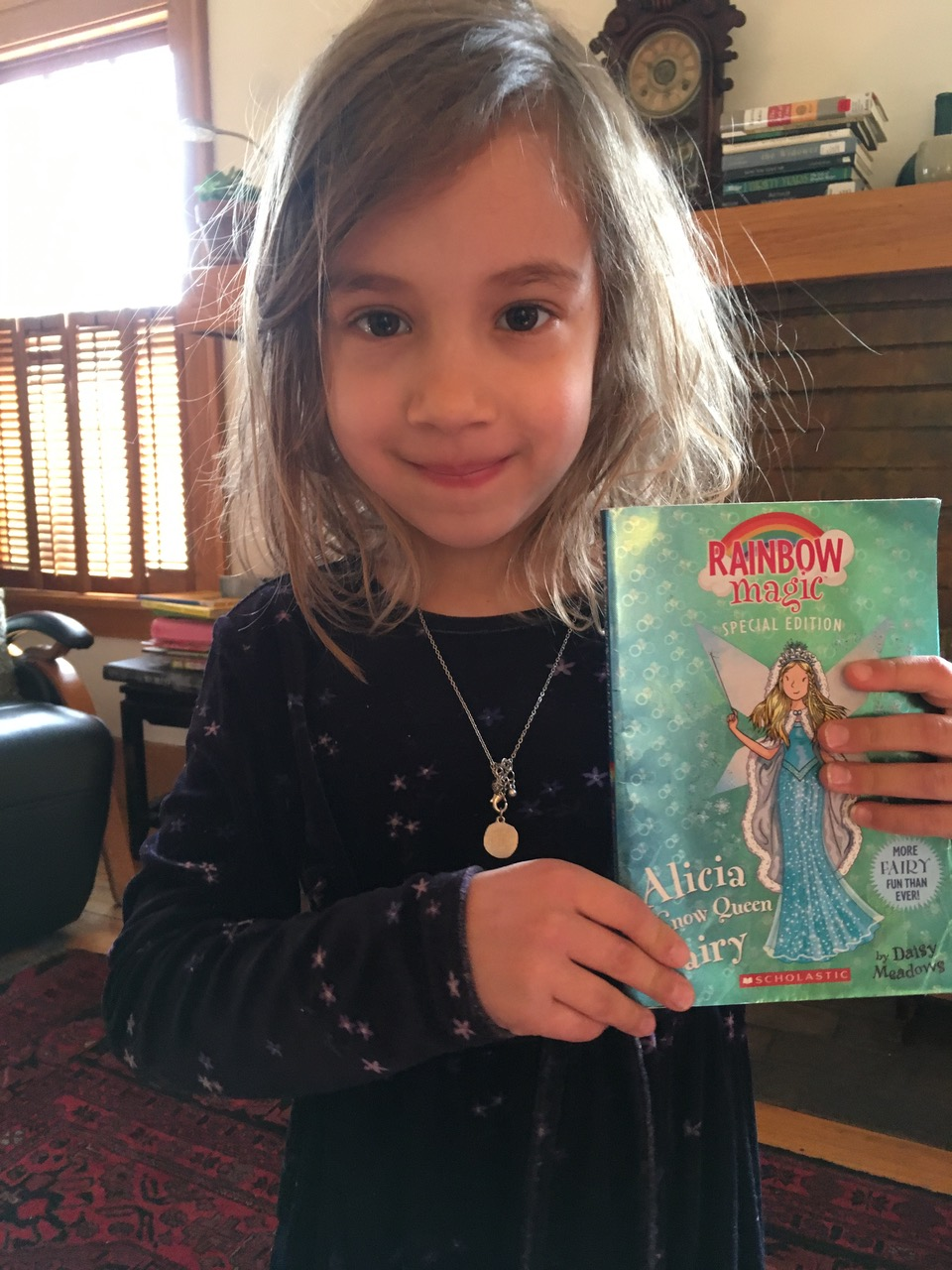 Rosenwaike's child holding a Rainbow Magic book.