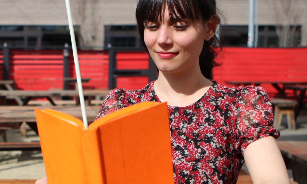 woman reading an orange book