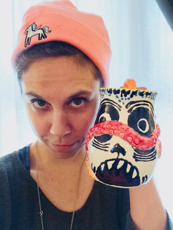 The author in an orange beanie holding a hand painted mug.